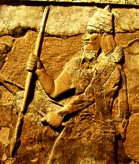 Stone wall carving showing warrior king with spear and bow