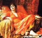 Woman dressed in luxurious red, lying on a silken couch